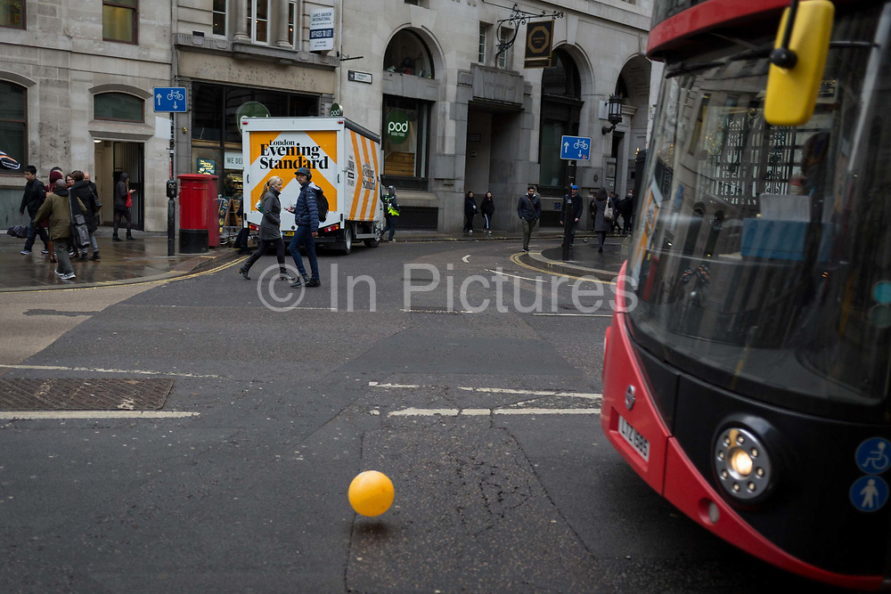 A London bus drives past a runaway yellow balloon floating along King William Street opposite Bank Underground station in the City of London, the capitals financial district, 7th March 2018, in London England.