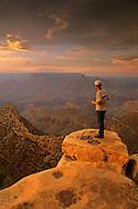 Tourist views sunset at Grand Canyon, from Grandview Point, South Rim, Grand Canyon Nat'l. Park, ARIZONA