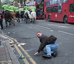 © Licensed to London News Pictures. 10/05/2016. LONDON, UK. At West Ham United fan tries to stand his ground as Mounted Police charge down the Barking Rd in an attempt to disperse West Ham United fans who were celebrating the clubs final game at the Boleyn Ground against Manchester United. Photo credit: LNP