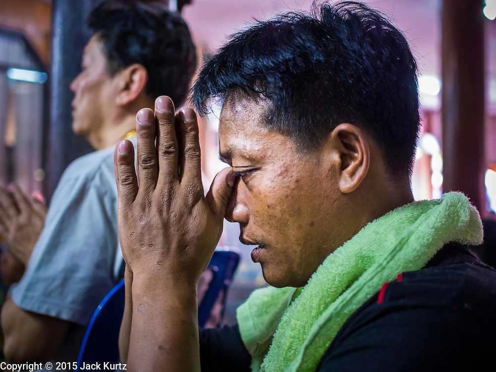 """06 APRIL 2015 - CHIANG MAI, CHIANG MAI, THAILAND: A Tai Yai (Shan) man prays in the prayer hall at Wat Pa Pao during the ordination of boys on the last day of the three day long Poi Song Long Festival in Chiang Mai. The Poi Sang Long Festival (also called Poy Sang Long) is an ordination ceremony for Tai (also and commonly called Shan, though they prefer Tai) boys in the Shan State of Myanmar (Burma) and in Shan communities in western Thailand. Most Tai boys go into the monastery as novice monks at some point between the ages of seven and fourteen. This year seven boys were ordained at the Poi Sang Long ceremony at Wat Pa Pao in Chiang Mai. Poy Song Long is Tai (Shan) for """"Festival of the Jewel (or Crystal) Sons.  PHOTO BY JACK KURTZ"""