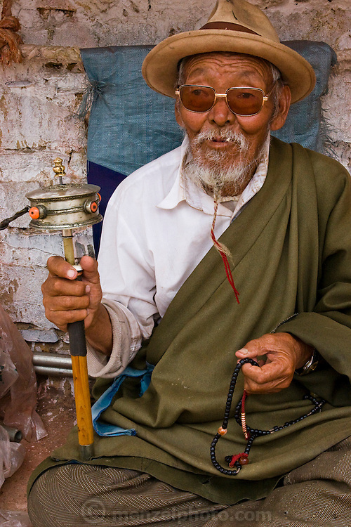 An elderly man with a prayer wheel and prayer beads at a small monastery near the Jokhang, Lhasa, Tibet.
