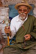 An elderly man with a prayer wheel and prayer beads at a small monastery near the Jokhang, Lhasa, Tibet.