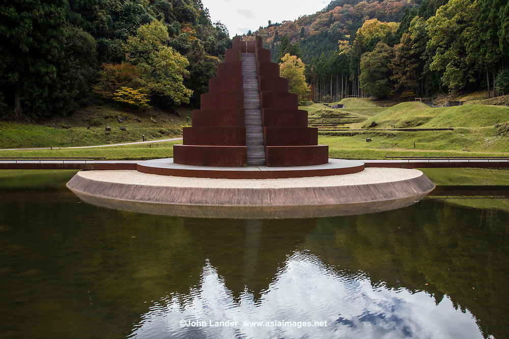 """Murou Art Forest is a feast for the eyes in a remote location of Nara Prefecture.  This outdoor sculpture and modern Japanese garden is found in Muro Village.  It is filled with giant sculptures designed by the Israeli sculptor Dani Karavan in 2006.  The designer, Karavan, is known for his amazing and monumental landscapes. Karavan gained international recognition for placing extraordinary art works in public places so he was a perfect choice to turn this area into an art trail - the theme of which is to bring nature and art together.  The first sculpture the Spiral Bamboo Forest with an entrance surrounded by bamboo trees with metal spiral stairs leading deep into the ground.  Afterwards, the path leads to the undulating Spiral Canal - a channel to that is a protection from rain.  Next on the trail is Sun Island, a circular staircase tower where the sunlight creates a thin line of bright light. It is in the middle of a pond though you can walk to the top.  The next scenic architecture is Stage Island with a circular wooden stage in the middle of another pond complete with a semicircle of seats - a great spot for outdoor performances. Then there is Pyramid Island, which is a large metal triangle in the pond near Stage Island. It is split right down the center making it two separate triangles. The last man-made island in the park is For the Birds which is simply trees and grass and not intended for park visitors, but as its name implies, it is """"for the birds"""" underscoring the theme of harmony with nature."""