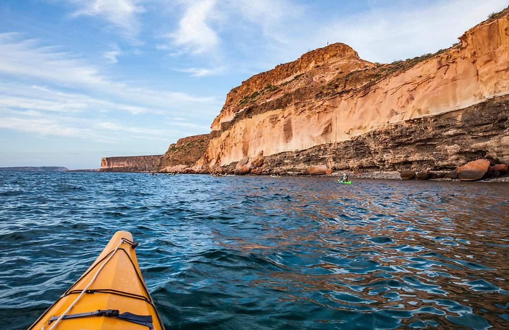 A guided sea kayaking tour offshore below towering sandstone cliffs on Isla Espirito Santo, Gulf of California, BCS, Mexico.