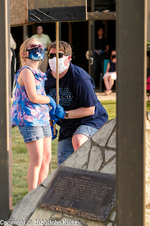 23 AUGUST 2020 - WEST DES MOINES, IOWA: A man and his daughter ring the bell for the victims of COVID-19 at West Des Moines United Methodist Church. More than 100 people attended a memorial service at West Des Moines United Methodist Church for Iowans who have died from COVID-19. Iowa is one of the Midwestern states that has recorded an increasing number of COVID-19 infections. Since Friday, August 21, Iowa has recorded 1,448 new cases of COVID-19. More than 1,030 Iowans have died from COVID-19, the disease caused by the Novel Coronavirus (SARS-CoV-2) since the pandemic hit Iowa in March.    PHOTO BY JACK KURTZ