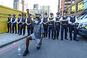 A man wearing a protective face mask kneels in front of police officers during a protest against the death in Minneapolis police custody of African-American man George Floyd near the U.S. Embassy, London, Britain, May 31, 2020. (Photo/ Vudi Xhymshiti)