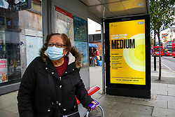 © Licensed to London News Pictures. 16/10/2020. London, UK. A woman wearing a face covering at a bus stop, with  the government's latest COVID-19 advert informing about the tier two restrictions, as London moves to COVID-19 tier two restrictions from tonight, following the government's announcement of tougher measures in the capital to manage increasing cases. From midnight tonight, households in London will not be allowed to mix indoors, including in pubs and restaurants.  Photo credit: Dinendra Haria/LNP