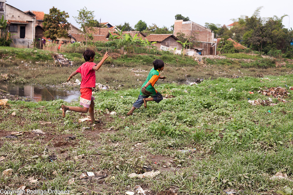 Boys chase each other and play with mud on the banks of the Citarum river near Cikarees, Bale Endah district, Bandung regency, Indonesia. ..The Citarum river, which runs about 270 kilometers through the province of West Java, is considered to be among the world's dirtiest. Over the last twenty years, the river has been severely polluted by toxic industrial waste, trash and raw sewage. The Citarum is one of the main sources of freshwater for West Java and supplies about 80% of water for Indonesia's capital Jakarta.