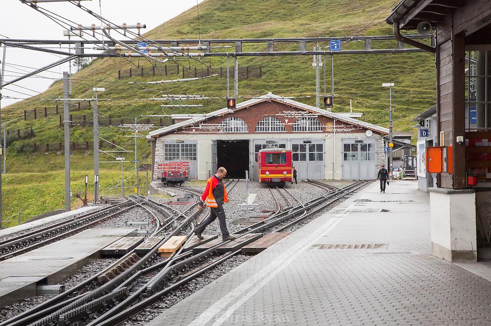 Workman crossing the tracks at the train station in Kleine Scheidegg, Switzerland