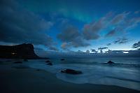 Early season northern lights - aurora borealis in August twilight light at Myrland beach, Flakstadøy, Lofoten Islands, Norway
