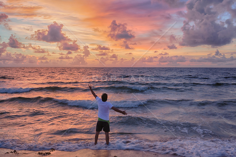 man standing in the Atlantic Ocean welcoming the sunrise in Fort Lauderdale, Florida