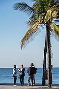 An Asian tourist sings Girl from Ipanema along Ipanema beach with Brazilian musicians in Rio de Janeiro, Brazil.