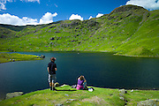 Tourists on nature trail in lakeland countryside at Easedale Tarn lake in the Lake District National Park, Cumbria, UK