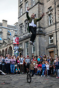 A juggler performs to a huge crowd in the Royal Mile during the Edinburgh Festival.