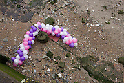 Birthday party balloons caught on the foreshore on the River Thames at Bermondsey, London.