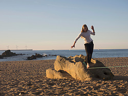 Teenage girl balancing along a slackline on a beach in Northern Spain