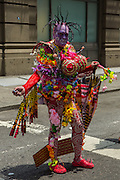 A spectator on a side street dressed in a multi-textured, multi-colored costume. A number of spectators were costumed.