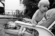 """A young girl of nearly four plays on garden furniture with her younger brother in the back garden of their South London house. The boy is blonde-haired with a healthy tummy storing energy for his games and boyhood fantasies while his sister lies on the soft cushion of the chair during this warm summer afternoon. From a personal documentary project entitled """"Next of Kin"""" about the photographer's two children's early years spent in parallel universes. Model released."""