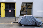 A small car is protected by plastic covering while parked on St John Street in Clerkenwell,  a on 26th February 2021, in London, England.