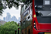 With the skyscrapers of the City of London, the capital's financial district, in the distance, a 33 London bus turns down Sydenham Hill, on 15th June 2021, in south London, England.