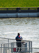 26 APRIL 2020 - DES MOINES, IOWA: A man fishes by himself on a walkway over the Des Moines River in downtown Des Moines. On Saturday, 25 April, there were 5,092 confirmed cases of COVID-19 in Iowa (an increase of 647 since Friday, April 24) and 112 deaths in Iowa caused by COVID-19.          PHOTO BY JACK KURTZ