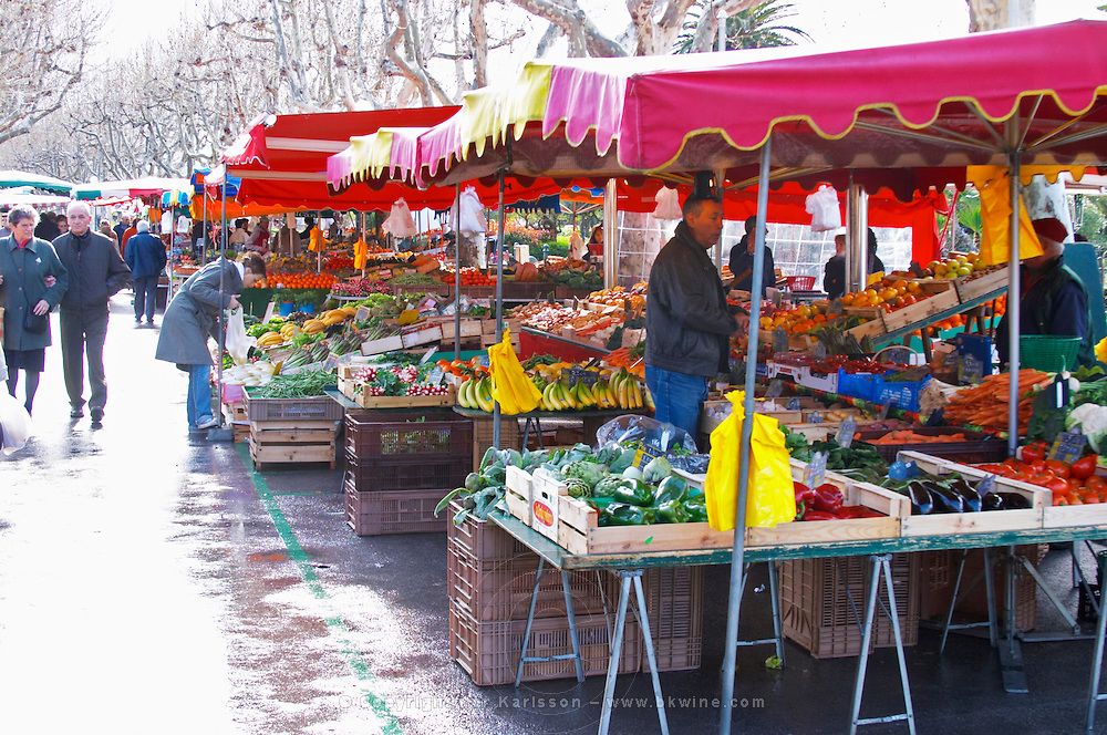 Street market merchant's stall with fruits and vegetables in rain Sanary Var Cote d'Azur France