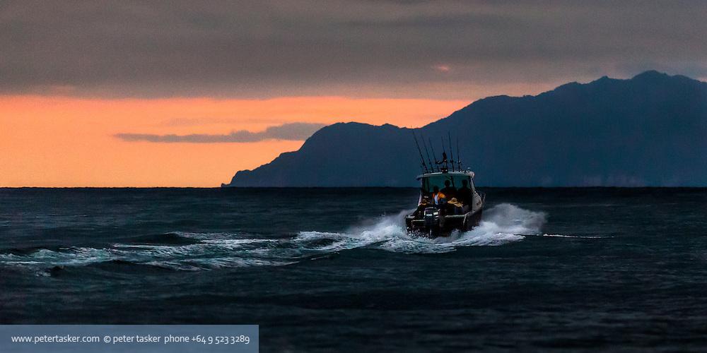 Fishing boat leaving Omaha Beach for Little Barrier Island, early morning. Hauraki Gulf, Auckland, New Zealand.