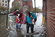 A couple wades through water to get to their apartment in Hoboken, New Jersey, Tuesday, October 30, 2012.  Photographer: Emile Wamsteker/Bloomberg News
