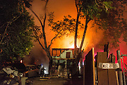 San Jose Fire Department works to put out a double house fire near Margaret St. and South 2nd St. in San Jose, California, on May 10, 2015. (Stan Olszewski/SOSKIphoto)