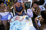 A baby lies on a table surrounded by his family as they enjoy a sunday afternoon at the beach, Salvador de Bahia, Brazil