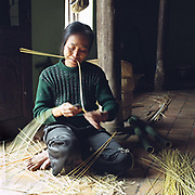 Woman preparing bamboo for weaving into baskets in Tang Tien village, Bac Giang province, Vietnam. With Vietnam's growing population making less land available for farmers to work, families unable to sustain themselves are turning to the creation of various products in rural areas.  These 'craft' villages specialise in a single product or activity, anything from palm leaf hats to incense sticks, or from noodle making to snake-catching. Some of these 'craft' villages date back hundreds of years, whilst others are a more recent response to enable rural farmers to earn much needed extra income.