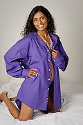 Woman wearing husband's purple shirt during a boudoir portrait session.