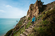 Woman walking and exploring the cliff paths near Beauport beach, with views out to sea in Jersey, Channel Islands