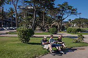 Sleeping man with a reading young man and lady, on a park bench at Estoril near Lisbon, Portugal.