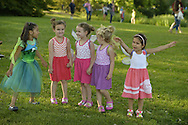 Old Westbury, New York, U.S. - June 21, 2014 - Wearing fairy wings are, L-R, PRISCILA BLANCHET, four years old, in green fairy costume; four-and-a-half-year-old triplets: ARIELLE KIRCHHOFER in orange dress, CRISTINA KIRCHHOFER in pink dress, BRIANNA KIRCHHOFER in purple dress; and JULIA DELGADO jumping up in peach dress. These best friends from Bayside, Queens came with their families to see the Lori Belilove & The Isadora Duncan Dance Company dance throughout the gardens during the Midsummer Night event at the Long Island Gold Coast estate of Old Westbury Gardens on the first day of summer, the summer solstice.