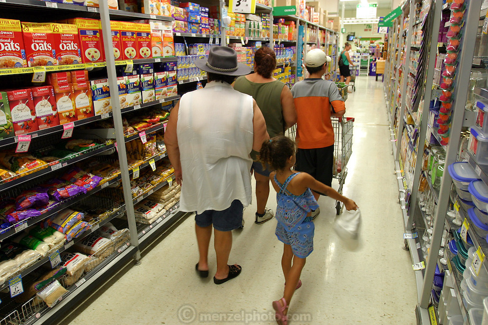 (MODEL RELEASED IMAGE). While the Browns of Riverview, Australia are used to living with a nearly-empty refrigerator in their rented home in Riverview, Australia (near Brisbane) they look forward to the days when it's full. Every two weeks a new check appears and the family goes to the supermarket. Here, Vanessa and John walk ahead with the shopping cart, while Marge and Sinead follow close behind. (Supporting image from the project Hungry Planet: What the World Eats.)