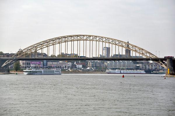 Nederland, Nijmegen, Waal, 21-10-2018Waalbrug bij Nijmegen bij extreem laagwater in de Waal en Rijn. Zicht op de stad terwijl een passagiersschip er onderdoor vaart.Foto: Flip Franssen