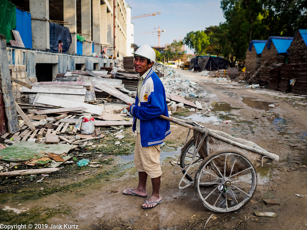 """12 FEBRUARY 2019 - SIHANOUKVILLE, CAMBODIA: A Cambodian construction worker walks through the the Blue Bay casino and resort development under construction in Sihanoukville. There are about 50 Chinese casinos and resort hotels either open or under construction in Sihanoukville. The casinos are changing the city, once a sleepy port on Southeast Asia's """"backpacker trail"""" into a booming city. The change is coming with a cost though. Many Cambodian residents of Sihanoukville  have lost their homes to make way for the casinos and the jobs are going to Chinese workers, brought in to build casinos and work in the casinos.      PHOTO BY JACK KURTZ"""