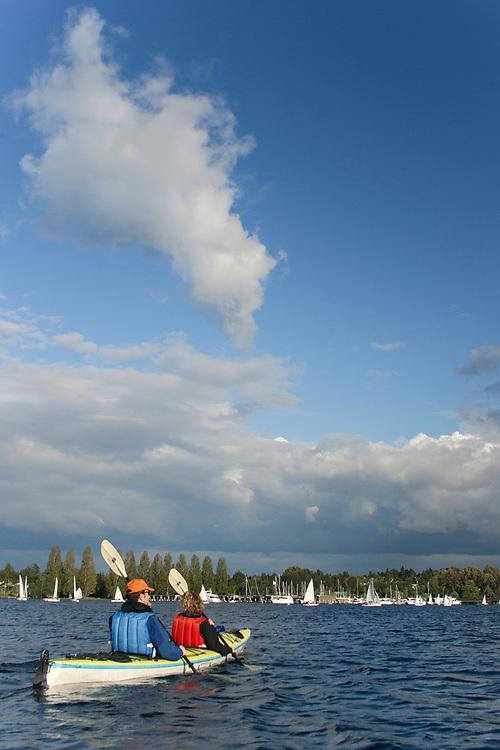United States, Washington, Seattle, couple kayaking in Montlake Cut between Lake Union and Lake Washington, near sailboats. MR