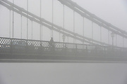© Licensed to London News Pictures. 11/12/2013. London, UK. A man woman cycles across  a fog covered Hammersmith Bridge.  Fog along the banks of the River Thames in Hammesmith, West London this morning 11th December 2013 . Photo credit : Stephen Simpson/LNP