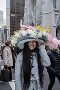 New York, NY, USA-27 March 2016. A woman wearing an elaborate hat with feathers, flowers and a bird's nest, and topped by a pink bird, in the annual Easter Bonnet Parade and Festival.