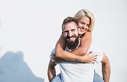 Happy woman enjoying piggyback ride on her boyfriend in front of wall, Bavaria, Germany