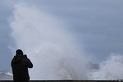 © Licensed to London News Pictures. <br /> 21/03/2015. <br /> <br /> Sandsend, North Yorkshire.<br /> <br /> A man takes a photograph as a huge wave crashes against the sea wall at Sandsend in North Yorkshire. The exceptionally high Spring tides were created by the moon's 18-year cycle.<br /> <br /> Photo credit : Ian Forsyth/LNP