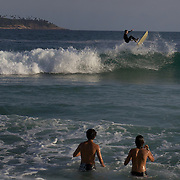 A late afternoon beach scene at Arpoador Beach as young surfers watch a surfer come to grief on a wave. Rio de Janeiro, Brazil. 8th August 2010. Photo Tim Clayton..