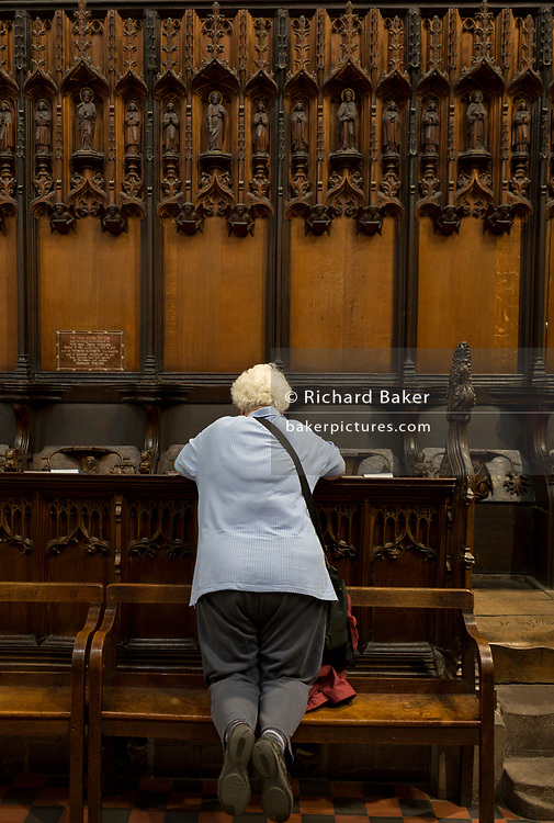 A lady visitor admires intricate wooden carvings in the choir of St. Laurence's Church, Ludlow, on 11th September 2018, in Ludlow, Shropshire, England UK.