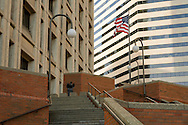 A US flag is flapping in the wind at the Henry M. Jackson Federal Building stairway Plaza with brass sculpture Philip McCracken's cast-bronze sculpture, Freedom (1976) depicts a bird breaking free from the bars of its cage.  A golden colored skyscraper fills the background, Seattle, WA, USA