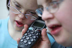 Teenage Downs Syndrome boy and girl listening on a large button telephone,