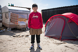 © London News Pictures. 29/04/2016. Calais, France. 11 year-old Unaccompanied child refugee Afghan boy Zyrat  outside the caravan he lives in at the calais Jungle. David Cameron has announced Britain will take in some child refugees living in camps inside the EU. Photo credit: Ben Cawthra/LNP