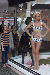 © licensed to London News Pictures. LONDON, UK  05/05/2011. Lingerie model Amanda-Jane (R) and head lingerie fitter Mina Abban-Mensah (2nd R) conduct a live bra fitting in the store window of Debenhams on Oxford Street. .85% of British women are thought to wear the wrong size bra. A fitting will take place on the hour until 4pm today. Please see special instructions for usage rates. Photo credit should read CLIFF HIDE/LNP