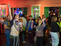 NEW ORLEANS - CIRCA FEBRUARY 2014: People looking up and raising hands to get beads in Bourbon Street during Mardi Gras celebrations in the French Quarter in New Orleans